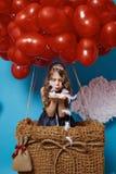 Le petit vol mignon de fille sur le coeur rouge monte en ballon le jour de valentines Photographie stock