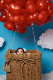 Le petit vol mignon de fille sur le coeur rouge monte en ballon le jour de valentines Image libre de droits