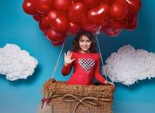 Le petit vol mignon de fille sur le coeur rouge monte en ballon le jour de valentines Photo stock