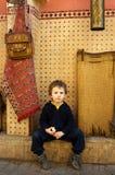 Le petit voyageur s'assied sur une rue à Marrakech Images stock