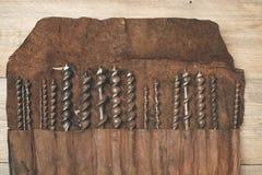 Le peu de foret dans l'outil en cuir roule sur un établi en bois Photographie stock libre de droits