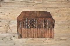 Le peu de foret dans l'outil en cuir roule sur un établi en bois Photo libre de droits