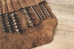 Le peu de foret dans l'outil en cuir roule sur un établi en bois Images stock