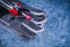Le peu de tournevis de Muunction fournit des gants de personnel de sécurité sur le backg métallique Images stock