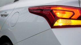 Le phare blanc du ` s de voiture est allumé le voyant de signalisation de direction clignote rouge Le feu de freinage banque de vidéos
