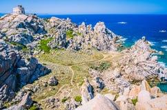Le phare blanc du Testa de capo en Sardaigne du nord, granit énorme bascule dans l'avant Photo libre de droits