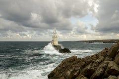 Le phare de mer de nuages bascule le bord de la mer Photo stock