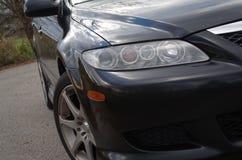 Le phare 2004 de passager d'avant de Mazda 6s (V6) et le Motegi mr7 roule Images stock