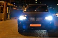 Le phare de voiture sur un brumeux temps de Soirée-nuit La voiture sur la route urbaine Nuit de soirée La nuit la voiture brûle v photo libre de droits