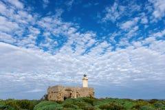 Le phare derrière la vieille maison Photographie stock libre de droits