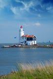 Le phare isolé se tient sur la broche en mer près du village Photographie stock