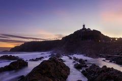 Le phare opacifie la mer de coucher du soleil Photos stock