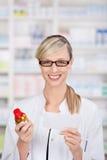 Le pharmacien féminin tient la prescription et la médecine photographie stock libre de droits