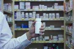 Le pharmacien tenant la bouteille blanche de vitamine devant l'officine rayonne Photographie stock