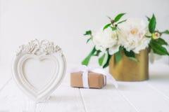 Le photoframe en forme de coeur avec des fleurs de plâtre, le boîte-cadeau avec le ruban et le vintage roulent avec le bouquet bl Image libre de droits
