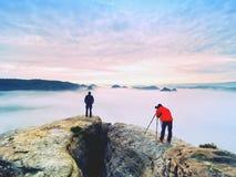 Le photographe avec l'oeil au viseur de l'appareil-photo sur le séjour de trépied sur la falaise et prend des photos, amis d'entr Images libres de droits