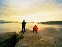 Le photographe avec l'oeil au viseur de l'appareil-photo sur le séjour de trépied sur la falaise et prend des photos, amis d'entr Photo libre de droits