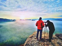 Le photographe avec l'oeil au viseur de l'appareil-photo sur le séjour de trépied sur la falaise et prend des photos, amis d'entr Photos libres de droits