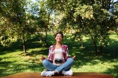 Le photographe de femme s'asseyant dehors en parc méditent photo stock