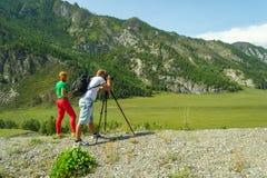 Le photographe de jeune homme et la fille d'une chevelure rouge voyage par A photos stock