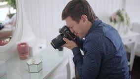 Le photographe masculin tire le mariage dans l'hôtel le plan rapproché d'anneau de mariage banque de vidéos