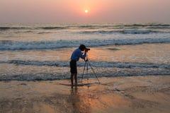 Le photographe photographie d'un trépied se tenant en mer Inde, Karnataka, Gokarna, février 2017 Images stock