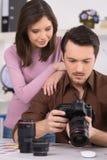 Le photographe regarde la photo sur l'appareil-photo. Photo libre de droits