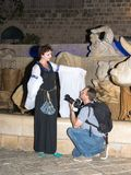 Le photographe s'est mis à genoux avant la fille - un membre des chevaliers du club de Jérusalem habillés dans le costume traditi photographie stock