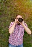 Le photographe se trouve sur l'herbe et prend des photos Vue de ci-avant Photographie stock libre de droits