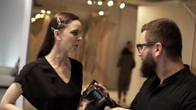 Le photorgapher barbu mignon dans le noir et la jeune femme discutent quelque chose banque de vidéos