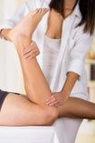 Le physio- thérapeute féminin remet travailler aux jambes masculines de patients, participation et recourbement, fond trouble de  Photographie stock