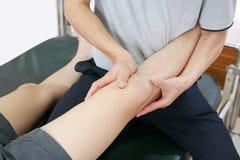 Le physiothérapeute traite la jambe au patient pour diminuer la douleur et pour améliorer la mobilité images libres de droits