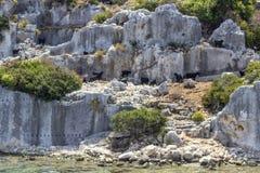 Le piccole capre nere scroccano sulle rovine storiche di Lycian vicino al mar Mediterraneo immagini stock libere da diritti