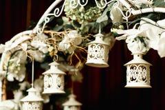 Le piccole lanterne di legno pendono da un altare di nozze Immagine Stock