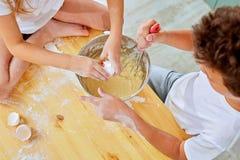 Le piccole mani dei bambini battono la pasta per i pancake che cucinano nella cucina immagini stock