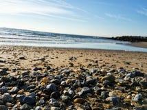 Le piccole pietre alla spiaggia di Brighton hanno catturato un giorno soleggiato fotografia stock