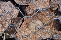 Le piccole pietre sono sotto i fili di ferro fotografia stock libera da diritti
