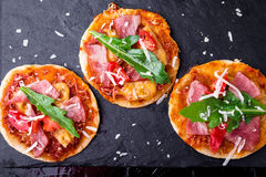 Le piccole pizze casalinghe con il prosciutto di Parma, il pomodoro, rucola sull'ardesia nera imbarcano Vista superiore fotografia stock