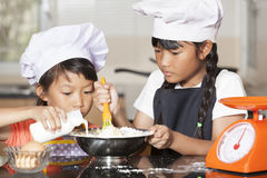 Le piccole ragazze asiatiche versano il latte nella farina e nell'uovo di frumento Fotografia Stock Libera da Diritti