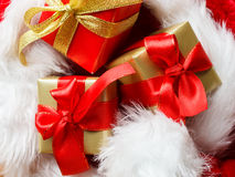 Le piccole scatole rosse e dorate con i regali hanno legato gli archi Immagine Stock Libera da Diritti