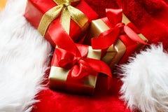 Le piccole scatole rosse e dorate con i regali hanno legato gli archi Fotografia Stock Libera da Diritti