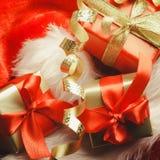 Le piccole scatole rosse e dorate con i regali hanno legato gli archi Fotografie Stock Libere da Diritti