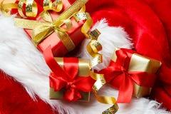 Le piccole scatole rosse e dorate con i regali hanno legato gli archi Fotografie Stock