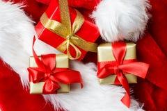 Le piccole scatole rosse e dorate con i regali hanno legato gli archi Immagini Stock
