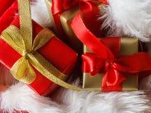 Le piccole scatole rosse e dorate con i regali hanno legato gli archi Fotografia Stock