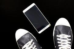 Le pied dans les espadrilles et le téléphone cassé sur le fond noir Images libres de droits
