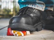Le pied dans une botte noire écrase un paquet de cigarettes photo stock