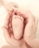 Le pied de la chéri de subsistance des mains de la mère avec soin Photographie stock libre de droits