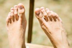 Le pied de la femme sur la chaise en bois extérieure photographie stock libre de droits