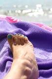 Le pied de la jeune femme avec l'émail de clou Photo stock